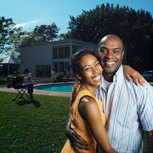 mid adult couple smiling and holding each other in back garden with swimming-pool with boy in background barbequing : Stock Photo