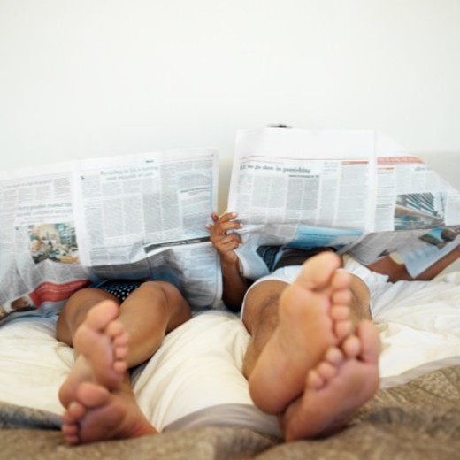 Stock Photo: 1491R-01205 low angle view of a couple reading newspapers while lying in bed