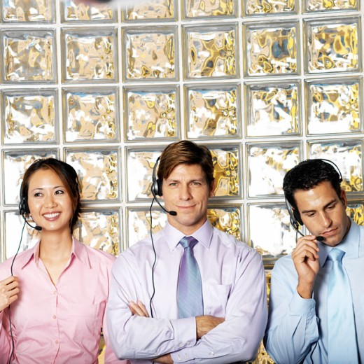 three businesspeople wearing telephone headsets standing against glass wall portrait : Stock Photo