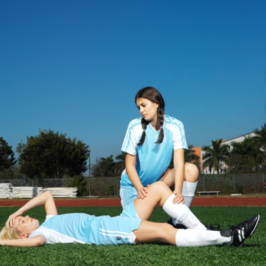 female soccer player (16-18) lying on ground injured with teammate (16-18) holding her knee : Stock Photo