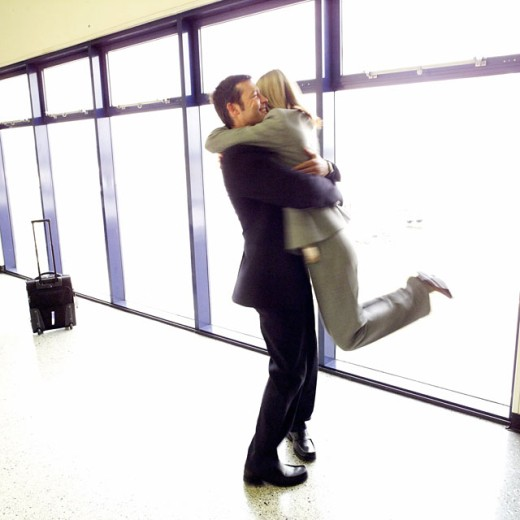 businesswoman hugging businessman at airport just after arriving : Stock Photo