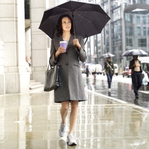 Stock Photo: 1491R-01319 front view of businesswoman walking in the street in the rain holding umbrella and a takeaway coffee