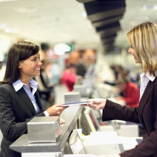 side view of businesswoman checking in at airport and stewardess checking ticket : Stock Photo