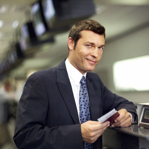 close up portrait of businessman checking in at airport with his ticket : Stock Photo