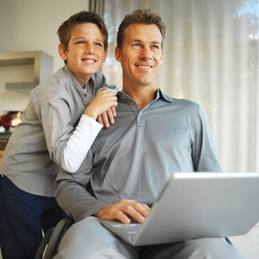 man in a wheelchair showing his son (10-11) something on a laptop : Stock Photo