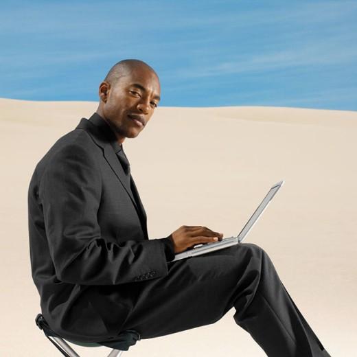 businessman in desert working on laptop computer, side view, portrait : Stock Photo