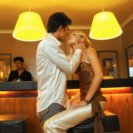 side view of young man and young woman kissing at the bar : Stock Photo