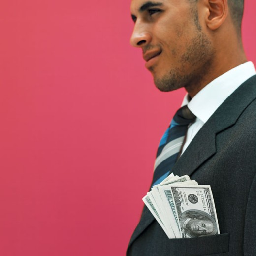 close up side view of businessman showing American dollar notes in his jacket pocket : Stock Photo