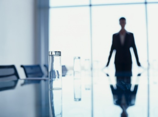 Stock Photo: 1491R-02926 close-up of a glass with a person standing in a board room