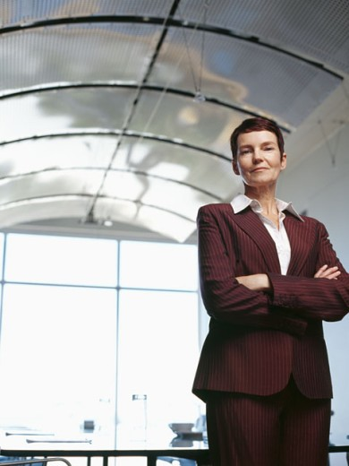 portrait of a businesswoman standing in an office with her arms crossed : Stock Photo