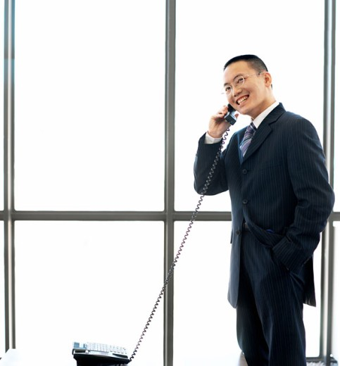 businessman standing talking on telephone : Stock Photo