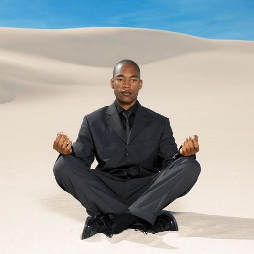 businessman doing yoga in the desert portrait : Stock Photo
