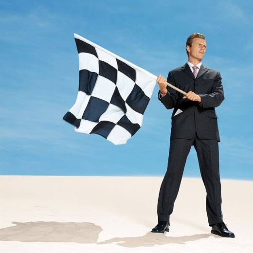 businessman in desert waving chequered flag, low angle view : Stock Photo