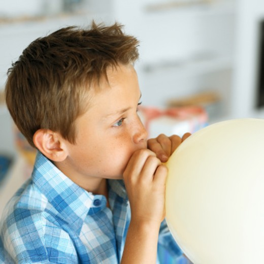 side view of a boy (8-9) blowing up a balloon : Stock Photo