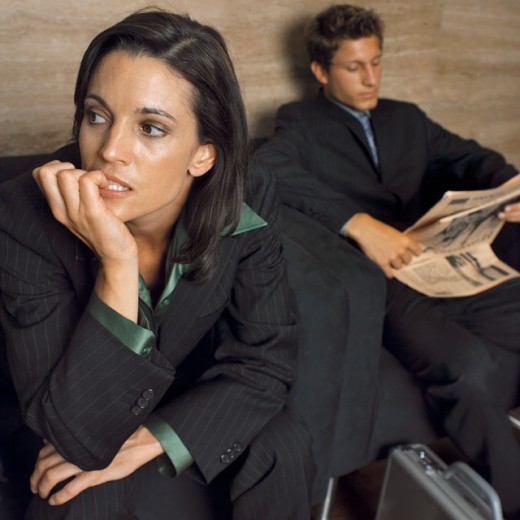 Stock Photo: 1491R-034 close up of a businesswoman sitting nervously and a businessman sitting reading newspaper