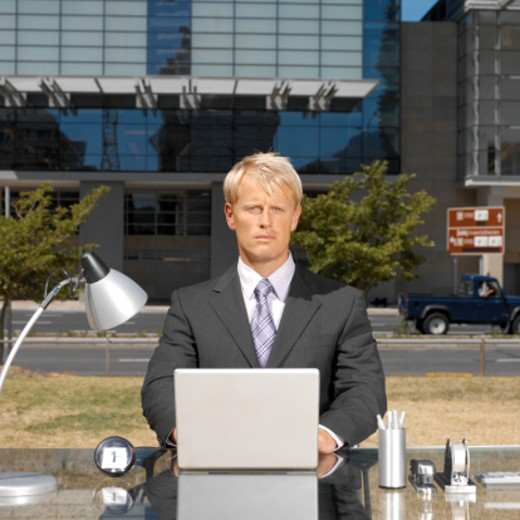 businessman sitting outdoors at desk with laptop : Stock Photo