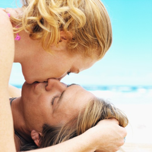 young man lying on beach young woman lying on top of him kissing, close up : Stock Photo