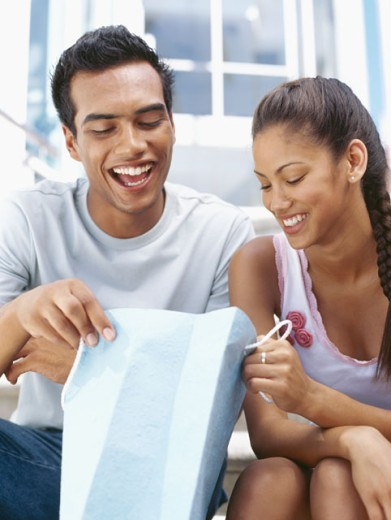 young couple looking in a shopping bag : Stock Photo