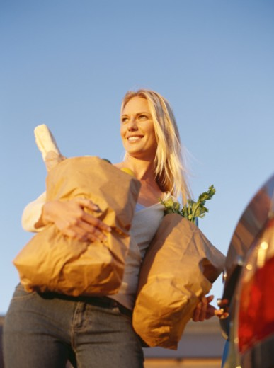 low angle view of a mid adult woman carrying paper bags : Stock Photo