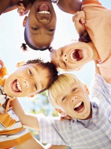low angle view of two girls and two boys standing in a huddle : Stock Photo