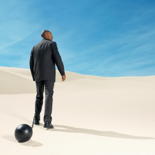 businessman wearing ball and chain in desert rear view, low angle view : Stock Photo