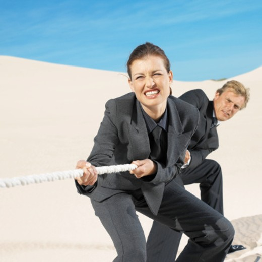 Stock Photo: 1491R-0380 businesspeople playing tug of war in desert