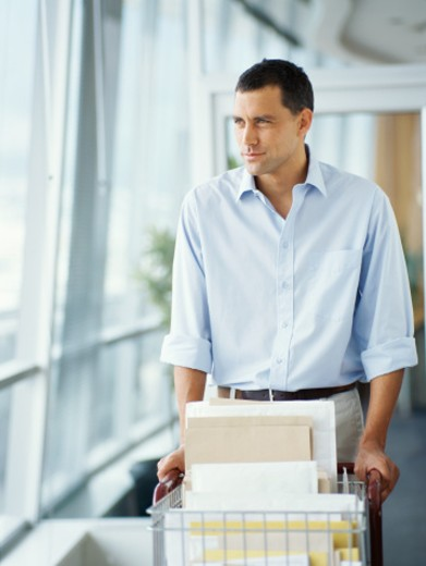 delivery man pushing a cart in an office : Stock Photo