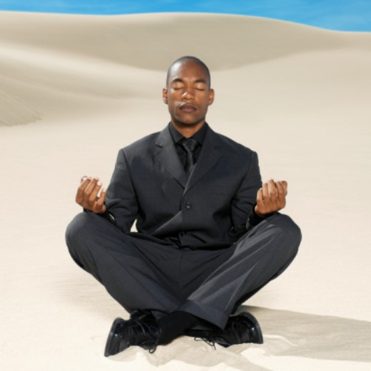 businessman doing yoga in the desert : Stock Photo