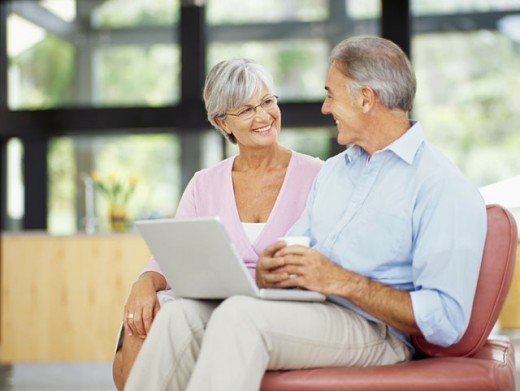 mature couple sitting together with a laptop : Stock Photo