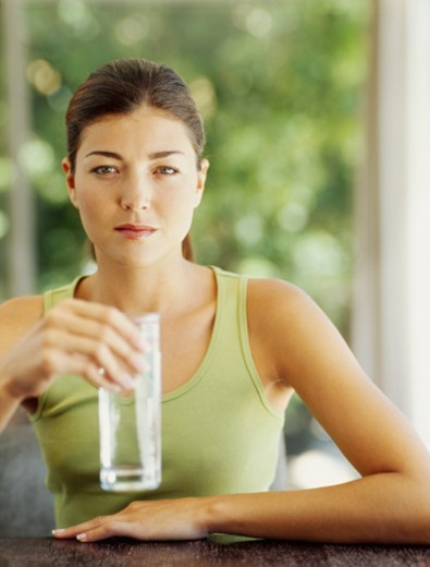portrait of a young woman holding a glass of water : Stock Photo
