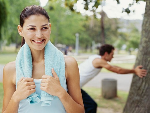 young woman smiling in a park with a towel around her neck : Stock Photo
