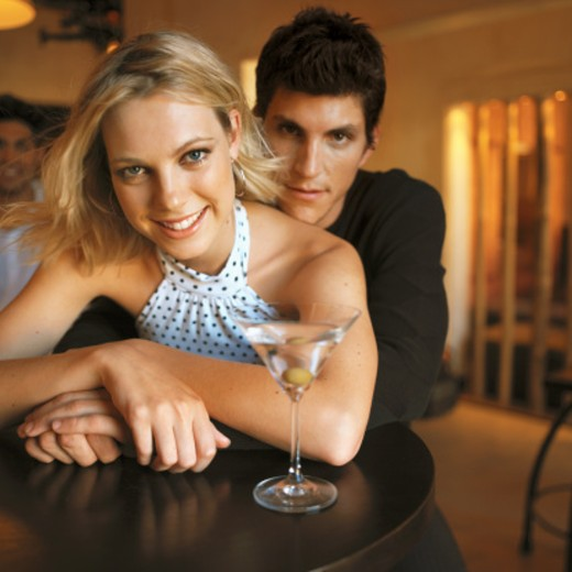 close up front view portrait of young man and young woman sitting at table with glass : Stock Photo