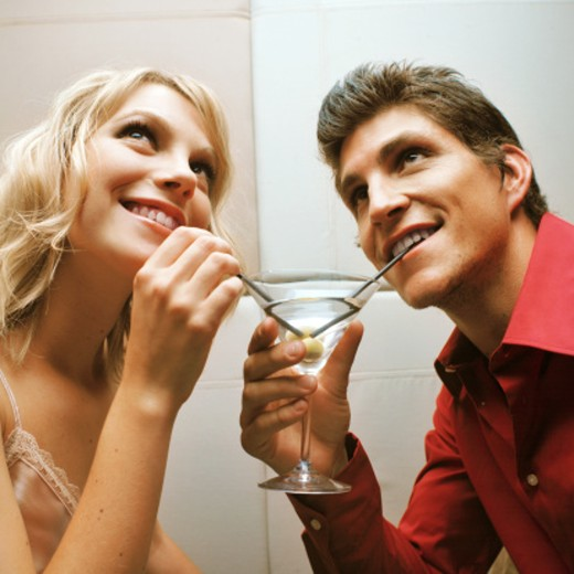 Stock Photo: 1491R-0458 close up side view of young man and young woman sharing drink