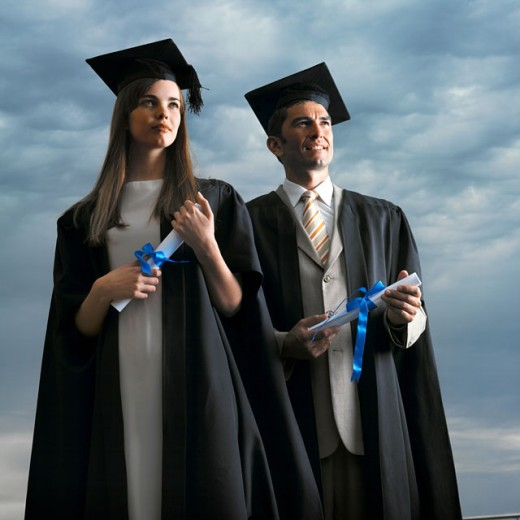 young man and young woman standing wearing cap and gown holding certificates : Stock Photo