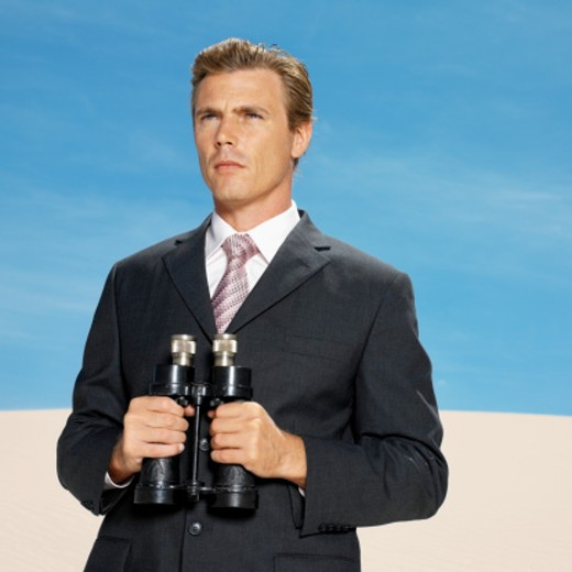 businessman in desert holding binoculars, low angle view : Stock Photo