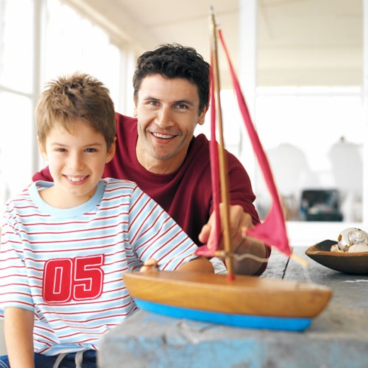 front view portrait of father and son (8-9) sitting fixing toy boat : Stock Photo
