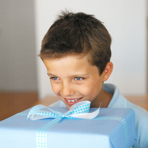 front view close up of a boy (8-9) holding a gift : Stock Photo