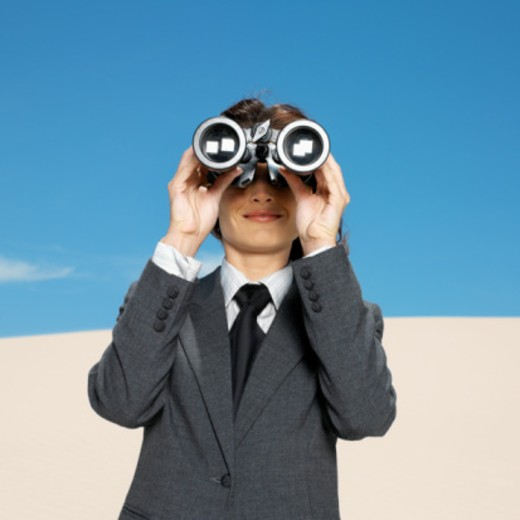 businesswoman in desert looking through binoculars low angle view : Stock Photo