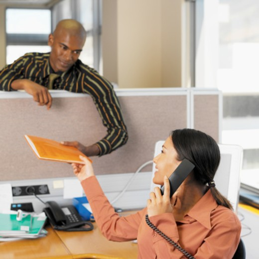 Stock Photo: 1491R-0603 businessman standing taking file from businesswoman while she talking on the telephone