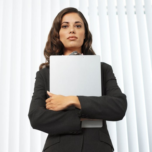 Stock Photo: 1491R-0617 low angle view of a serious businesswoman holding a clipboard