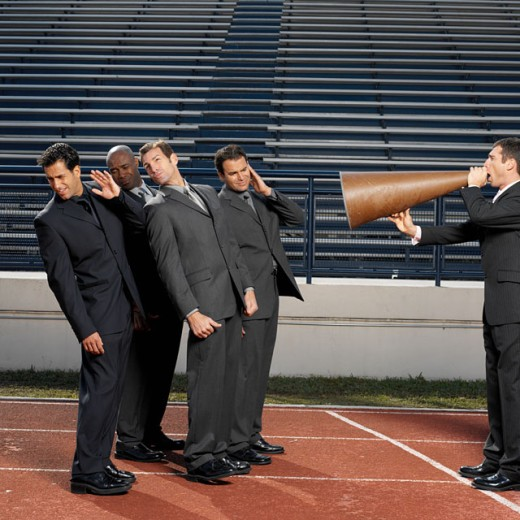 Stock Photo: 1491R-0618 businessman talking through megaphone to businesspeople, side view