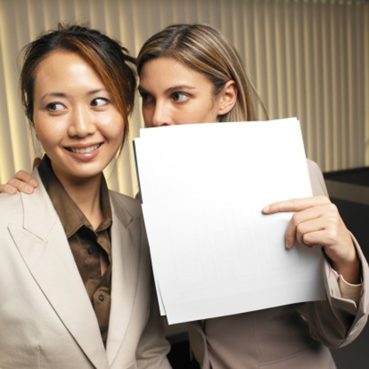 Stock Photo: 1491R-0640 businessman looking suspiciously over his shoulder rear view