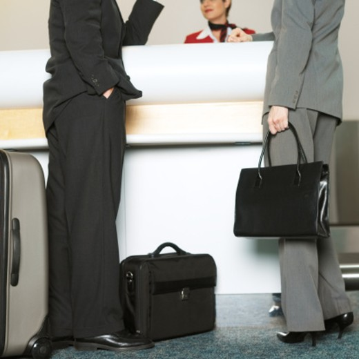 low section of businesswoman and businessman checking in at desk to stewardess : Stock Photo