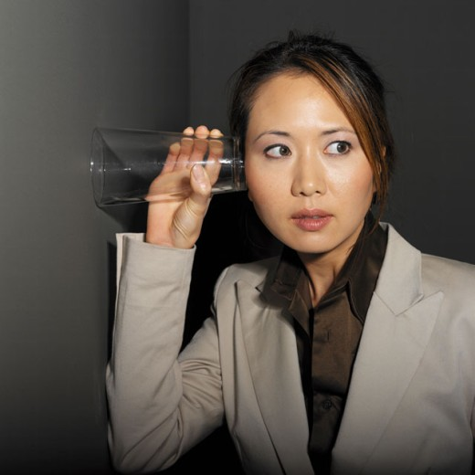 Stock Photo: 1491R-0788 businesswoman eaves-dropping in office by holding glass to the wall portrait close-up
