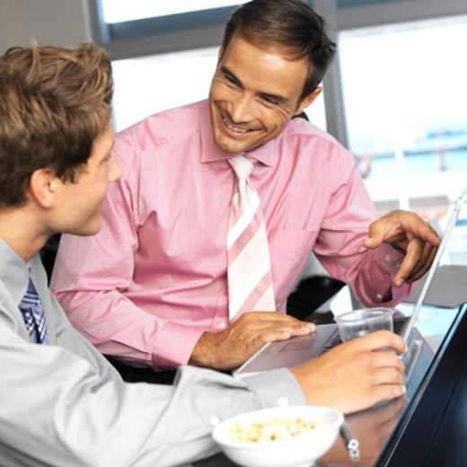 close up of two businessmen holding a glass working on the laptop and a bowl of peanuts : Stock Photo