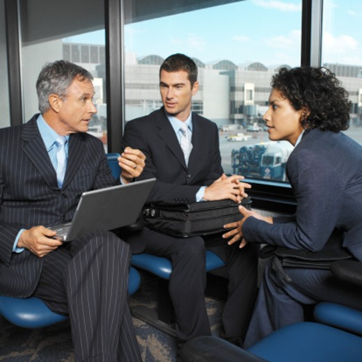 two businessmen and one businesswoman having meeting in airport terminal : Stock Photo