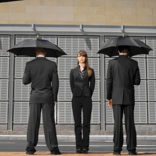 Stock Photo: 1491R-086 two businessmen facing away holding umbrellas and businesswoman front view