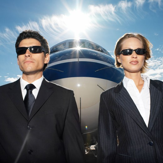 close up portrait of businessman and businesswoman standing in front of airplane : Stock Photo