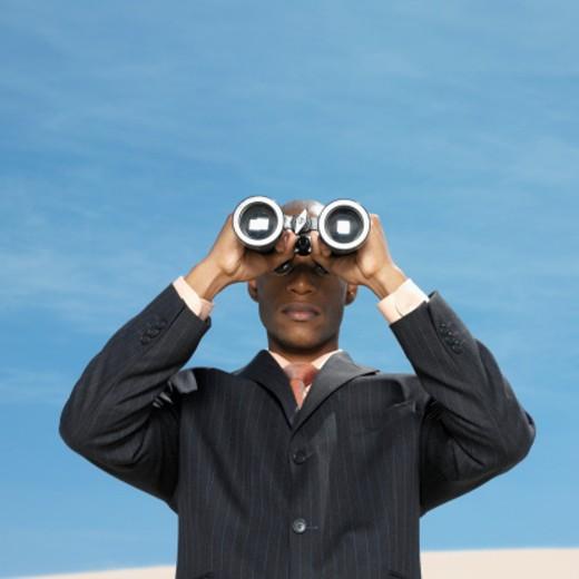 businessman in desert looking through binoculars : Stock Photo