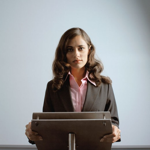 portrait of a businesswoman standing at a podium : Stock Photo